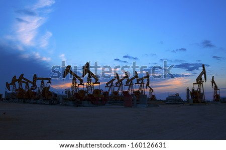 Oil pump oil rig in the sunset background for design