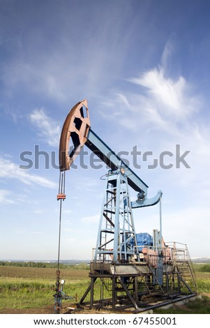 Oil pump on a green field - stock photo