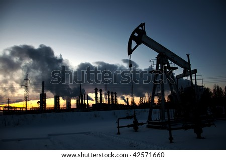 oil pump on  background of  industrial landscape and winter sky in  smoke - stock photo
