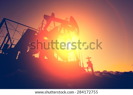 Oil pump on background of red (orange) sky - stock photo