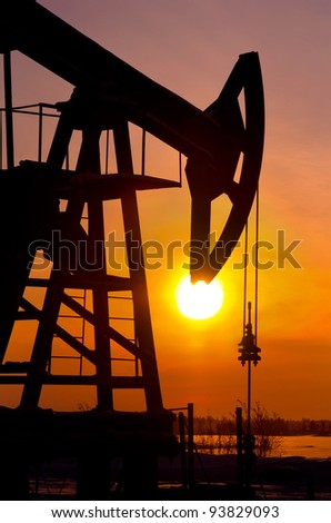Oil pump rocker close to sunrise background - stock photo