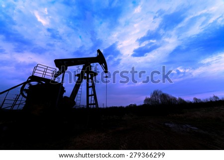 oil pump silhouette against blue sky - stock photo