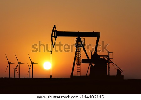 oil pump silhouette and alternative energy in a sunset background - stock photo