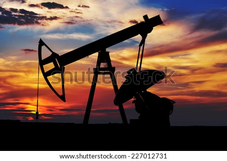 Oil Pump Silhouette at sunset - stock photo