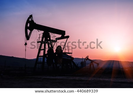 oil pump silhouette on the beautiful red sunset - stock photo