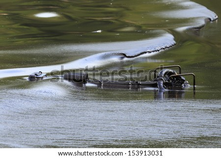 Oil pump soaked in crude oil spilled on the beach of Thailand - stock photo
