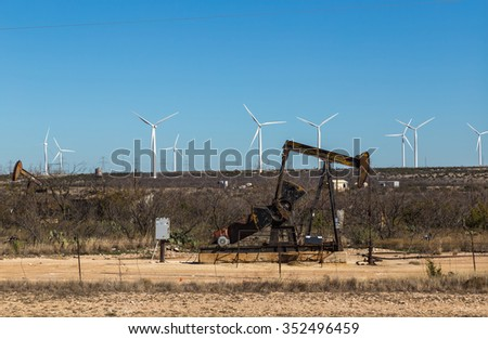 Oil pumping equipment juxtaposed with field of wind turbines against clear blue sky. Power transmission lines in distance.  - stock photo