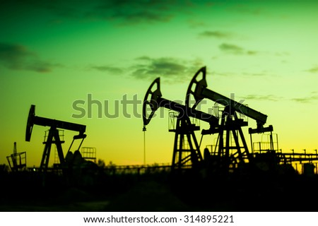 Oil pumps at sunset sky background. Selective focus, shallow depth of field. - stock photo