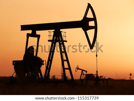 Oil pumps silhuettes operating at sunset time - stock photo