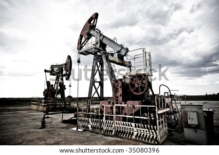 Oil pums in the fields cold contrast giving techno mood against dramatic cloudscape - stock photo