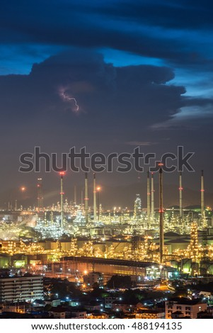 Oil refinery against the blue hour after the sunset with a small line of lightning