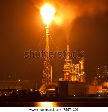 Oil refinery at night creating a huge smoke cloud with reflections on the nearby ocean - stock photo