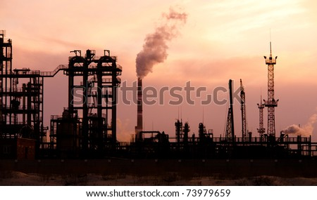 Oil refinery at sunset. Enviroment pollution. - stock photo