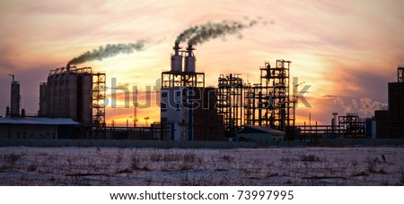 Oil refinery at sunset. Enviroment pollution.