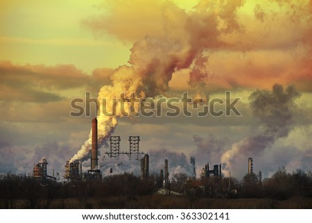 Oil refinery at sunset spewing gases from smoke stacks - stock photo