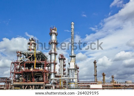Oil refinery building under cloudy sky - stock photo
