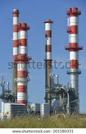 Oil refinery, Europe. Polluting energy. Symbology with stop sign. Vertical shoot