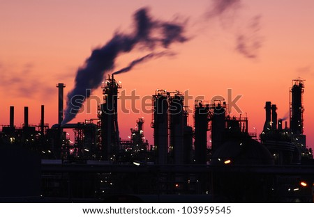 Oil refinery factory silhouette over sunset - stock photo