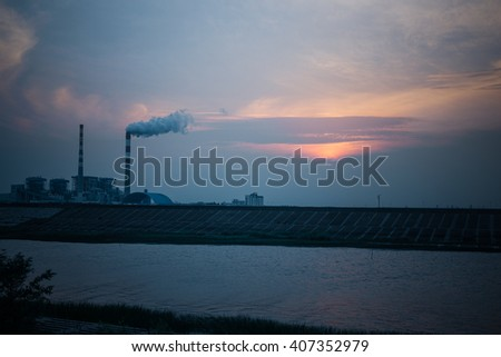 oil refinery factory under the cloudy sky,near by a river. - stock photo