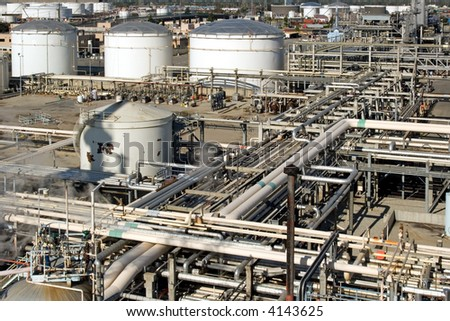 Oil refinery for making gasoline, diesel, and other fuels along with pollution and harm to the environment - stock photo