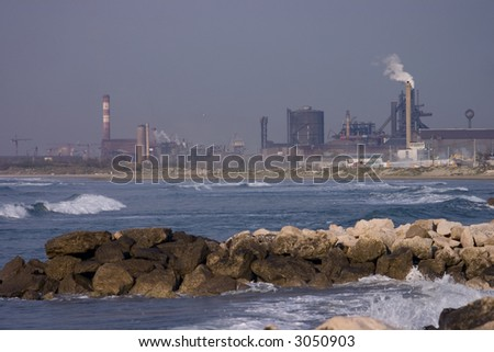 Oil refinery in the south of France, rocky beach, rough sea and a dark brooding sky. - stock photo