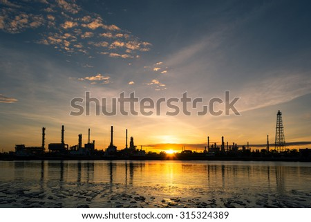 Oil refinery industry plant along twilight morning , Oil refinery factory in silhouette and sunrise sky - stock photo