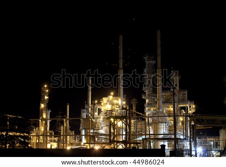 oil refinery lit up at night under mixed light