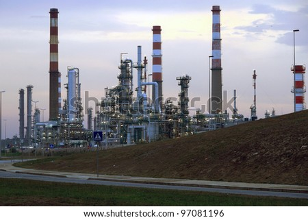 Oil refinery near a road in the early morning light (dawn) - stock photo