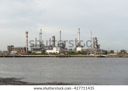 Oil refinery near water with blue sky - stock photo