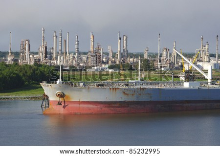 Oil refinery on the mississippi river near the gulf entrance with tanker ship in the foreground - stock photo