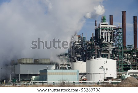 Oil refinery partially covered with smoke, with the clouds providing much room for copy space - stock photo