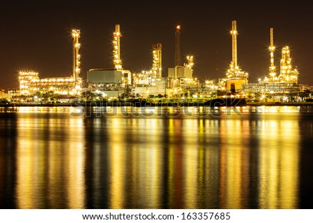Oil Refinery Plant along river with tanker loading - stock photo