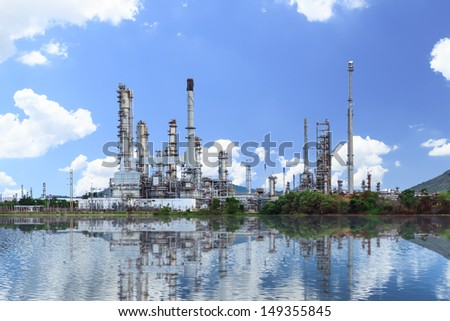 Oil refinery plant along the river with reflection - stock photo