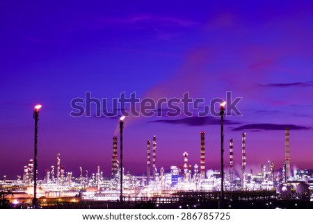 Oil refinery plant at night Fire and smoke comming out from chimneys - stock photo