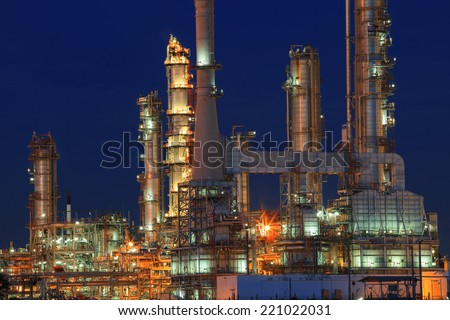 oil refinery plant in petrochemical industry estate at night time with blue sky background - stock photo