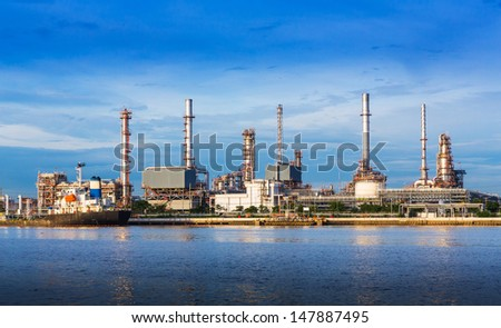 Oil refinery plant near river in evening sunlight