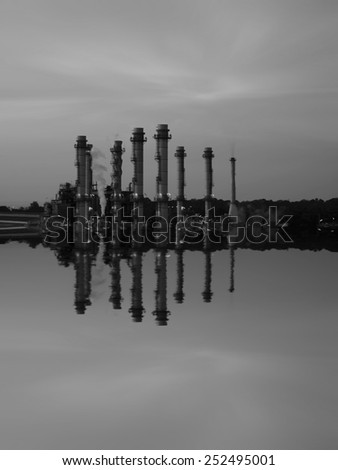 Oil Refinery reflected light water sunset industry in thailand black and white tone. - stock photo
