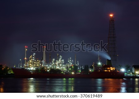 Oil refinery reflex on river at night.