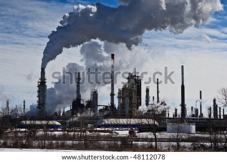 Oil refinery, smoke and smog pouring out of smoke stacks, against blue sky. - stock photo