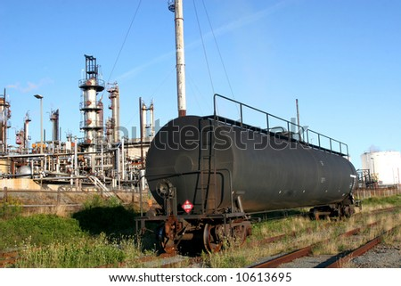 Oil refinery with rail tanker car in the foreground.