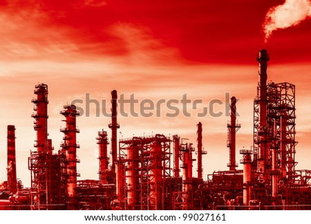 Oil refinery with smoke from the pipe. Black and white photography with red tint to show danger and global warming. - stock photo