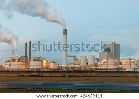 Oil refinery with smoking at twilight - stock photo