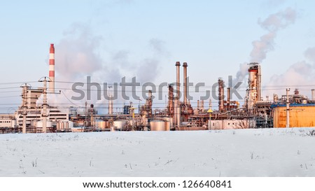 oil refinery with smoking chimneys in winter against blue sky - stock photo