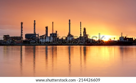 Oil refinery with water reflection at sunrise - stock photo