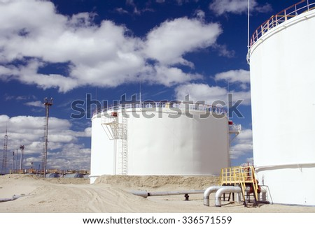 Oil reservoir. Oil and gas refinery plant. Industrial scene of oil field. Blue sky with clouds above gas station