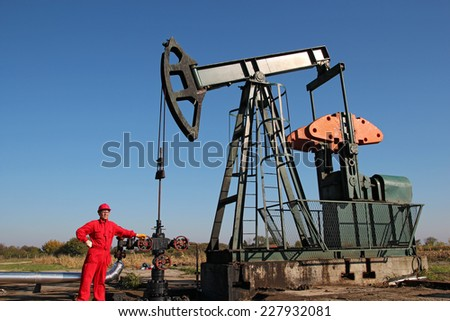 Oil Rig and Laborer. Oil and gas industry.  Worker in coveralls and safety goggles working on a drilling rig. - stock photo