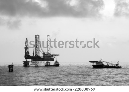 Oil rig and supply vessels - stock photo