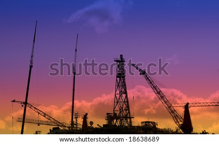 Oil Rig at Sunset with work going on throughout the night - stock photo