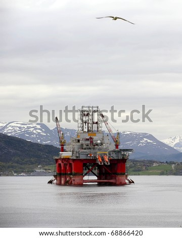 Oil rig between mountains in a norwegian fjord
