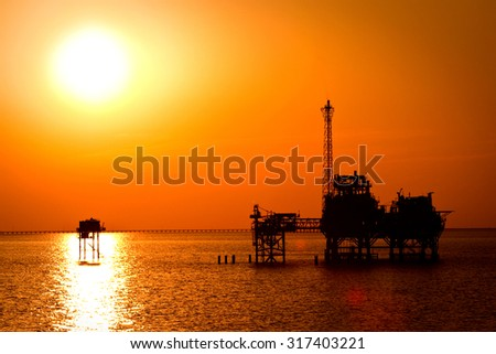 Oil rig in the sunset - stock photo